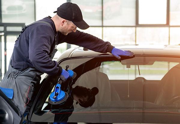 technician replacing car windshield