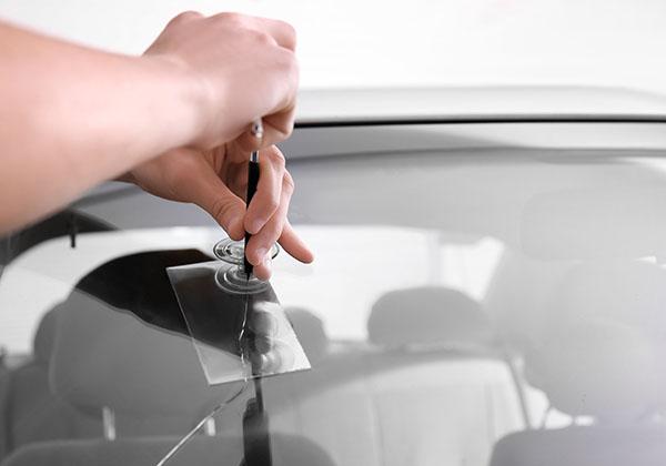 Technician fixing a crack in a car windshield